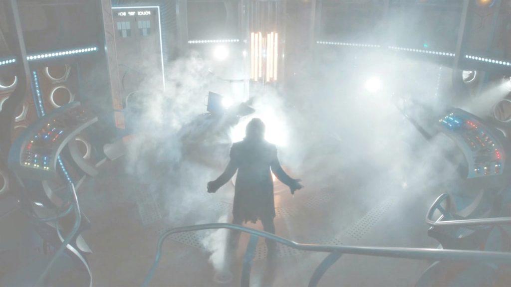 Kadr z odcinka Twice Upon a Time utrzymany w odcieniach beli, niebieskiego i brązu. Kadr przedstawia zamglone wnętrze TARDIS z drzwiami z tyłu odrobinę na lewo od środka, i stojącą pośrodku, trochę z przodu kadru Trzynastą Doktor - odwróconą do widza plecami - jeszcze w stroju Dwunastego Doktora.