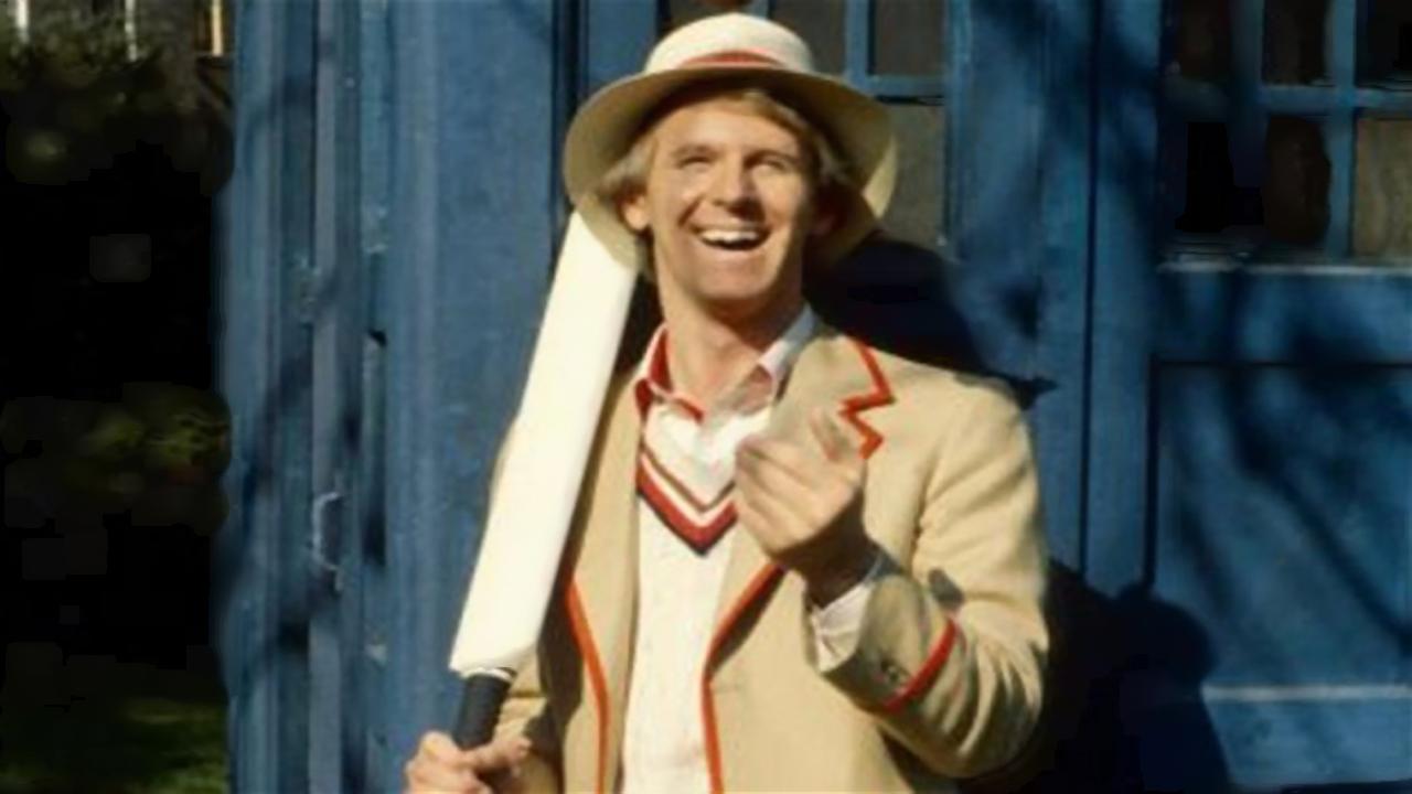 Piąty Doktor w świetle słońca, oparty o drzwi TARDIS