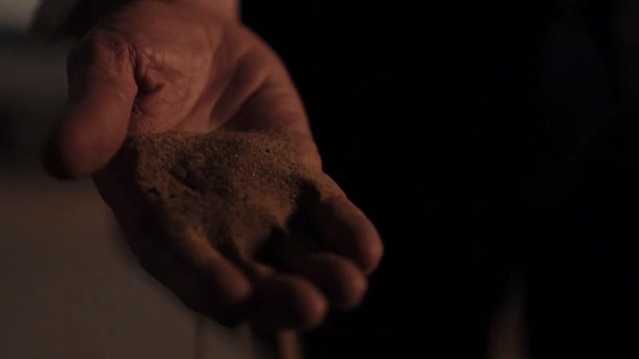 Dłoń Doktora, przez która przesypują się ziarnka piasku