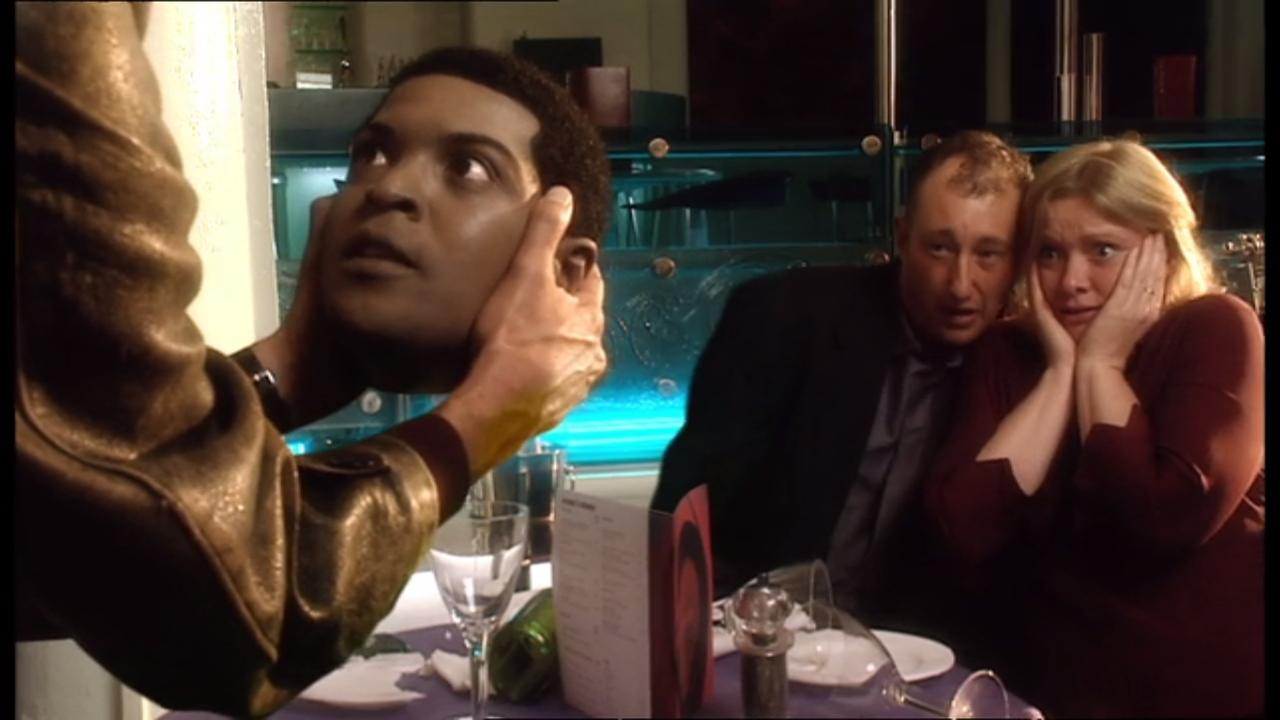 """Kadr z odcinka """"Rose"""": głowa fałszywego Micky'ego Smitha (Auton) w rękach Dziewiątego Doktora"""