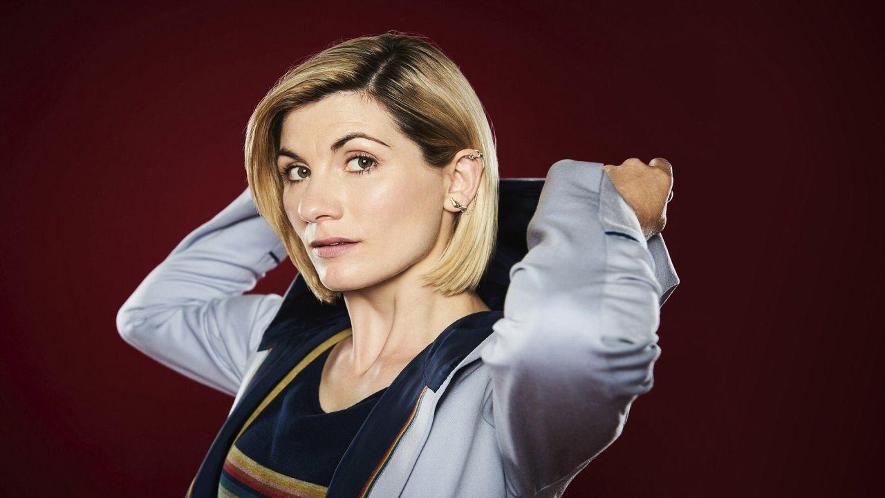 Zdjęcie promocyjne z Jodie Whittaker jako Trzynastą Doktor. Whittaker w stroju Doktor obrócona do ekranu lewym profilem podnosi kaptur swojego płaszcza.