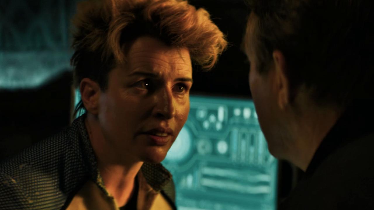 Na pierwszym planie, po lewej postać Angstrom, zwrócona w stronę Grahama, odwróconego do kadru tyłem. W tle błękitny ekran z kosmicznymi diagramami.