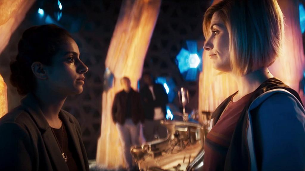 """Trzynasta Doktor i Yaz na pokładzie TARDIS. W tle: Graham i Ryan. Kadr z odcinka """"Demons of the Punjab""""."""