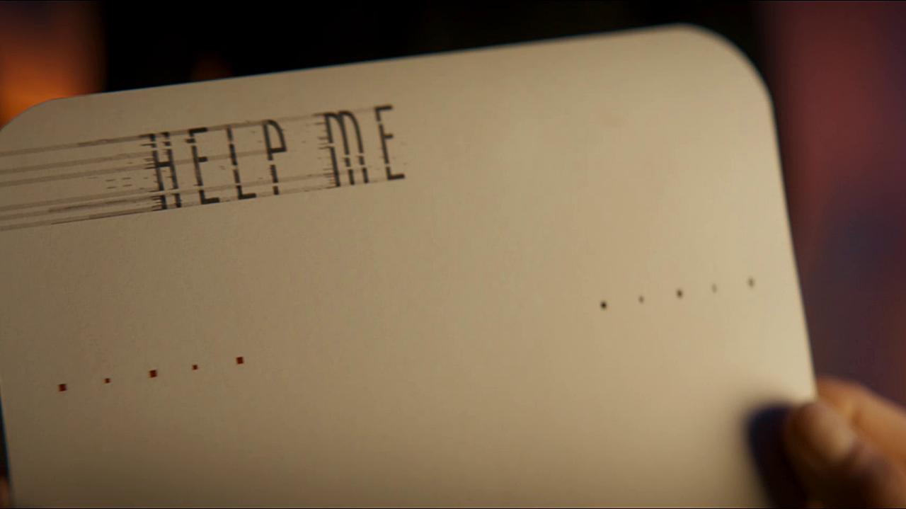 """Rewers białej karty adresowej z nadrukowanym, lekko rozmazanym od prędkości napisem """"Help me""""."""