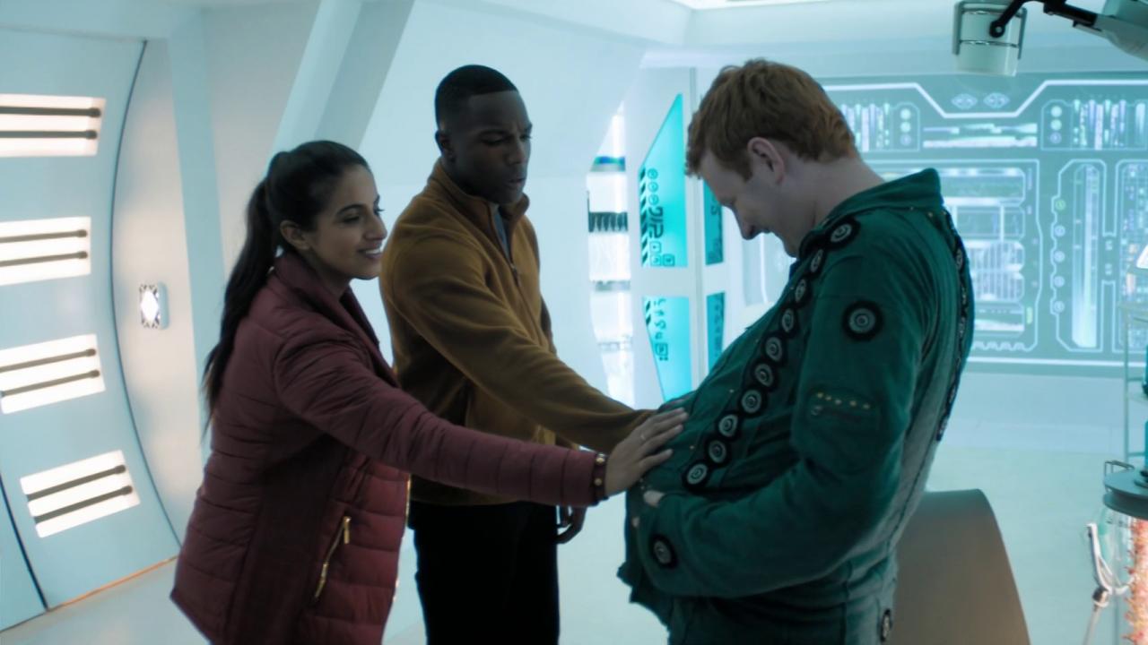 Od lewej Yaz w czerwonej kurtce, Ryan w żółtym swetrze i Ios w zielonym swetrze, stoją w białym pomieszczeniu. Yaz i Ryan dotykają brzucha ciążowego Iosa. Ios patrzy na swój brzuch z uśmiechem. Yaz się uśmiecha, Ryan ma zdziwiony wyraz twarzy.