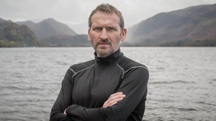 Na obrazie znajduje się Christopher Eccleston z założonymi rękami. Posiada on kilkunastodniowy zarost i jest ubrany w szarą dresową kurtkę. Za aktorem możemy dostrzec góry oraz morze/jezioro.