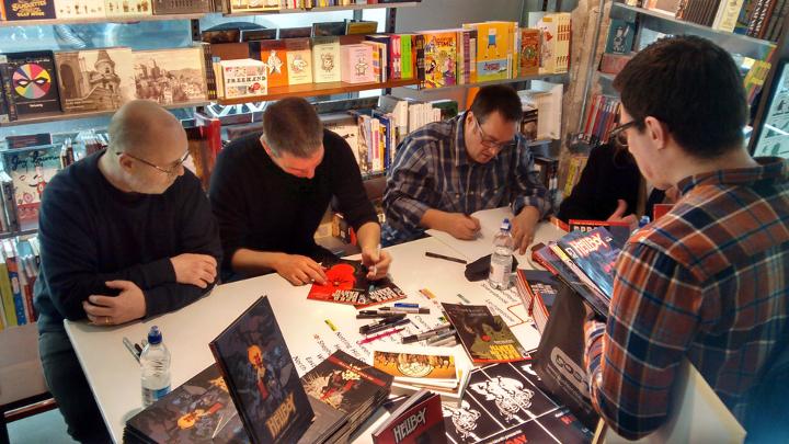 Twórcy komiksów podczas sesji autografowej. Zdjęcie przedstawia czterech mężczyzn znajdujących się najprawdopodobniej na otwartej przestrzeni. Trzech z nich podpisuje komiksy należące zapewne do osoby znajdującej się na pierwszym planie z prawej strony.