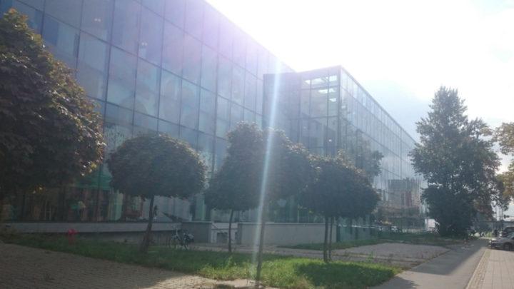 Na zdjęciu znajduje się Hala-Expo w Łodzi, na której odbył się MFKiG. Przeszklony budynek otoczony jest chodnikiem oraz kilkoma drzewami. Ponadto, zobaczyć możemy wyraźny promień słońca odbijający się od ścian wspomnianego miejsca.
